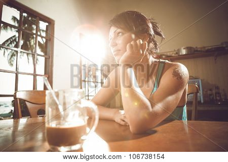 Blurred background of big window with beach landscape and brown desk top and woman at the table and sunlight
