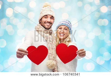 love, valentines day, couple, christmas and people concept - smiling man and woman in winter hats and scarf holding red paper heart shapes over blue holidays lights background