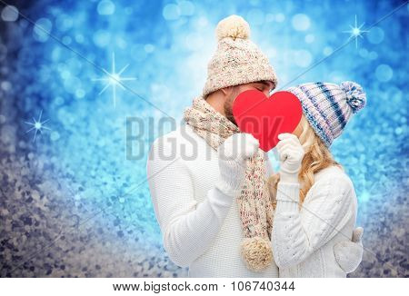 love, valentines day, couple, christmas and people concept - smiling man and woman in winter hats and scarf hiding behind red paper heart shape over blue glitter and holidays lights background
