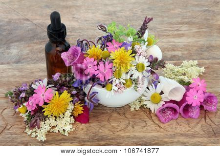 Herbal medicine flower and herb selection in a mortar with pestle and dropper bottle over hemp paper background.