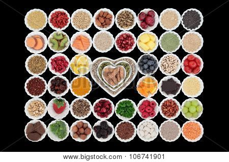Large healthy superfood collection in porcelain crinkle bowls over black background. High in vitamins and antioxidants.