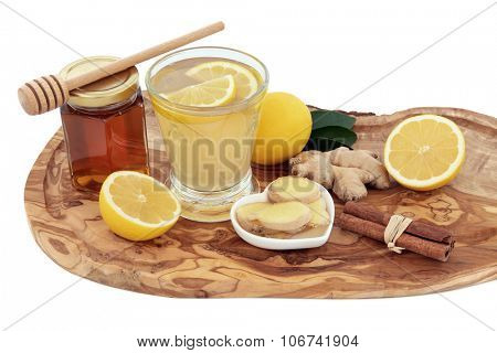 Cold and flu remedy cure drink in a glass with fresh ginger, lemon, honey in a jar with dropper and cinnamon spice on an olive wood board over white background.