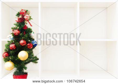 Christmas Tree On Empty White Bookshelf