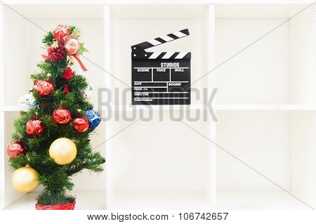 Christmas Tree And Movie Clapper On Empty White Bookshelf