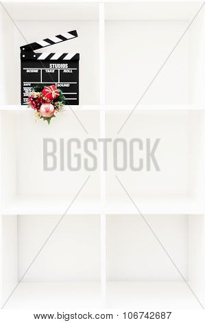 Movie Clapper Board With Christmas Decoration On Vertical White Bookshelf