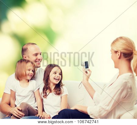 family, technology, ecology and people - smiling mother, father and little girls with camera over green background