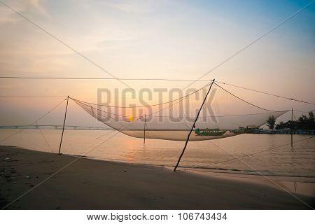 Calm scene of fishing net against purple sunset.