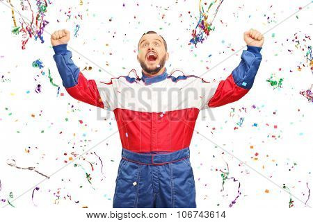 Overjoyed car racer in overalls celebrating victory with a bunch of confetti streamers around him isolated on white background