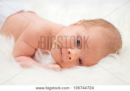 Little baby lying on a fur bedspread