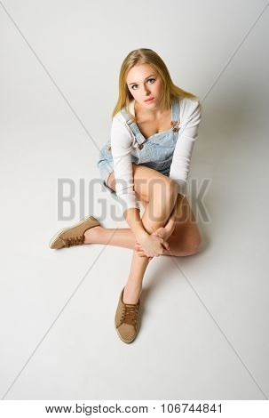 Young girl sit on the floor on light grey background