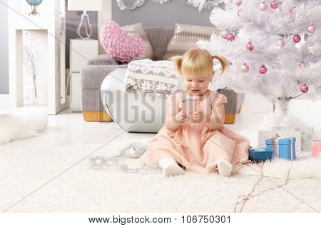 Pretty little girl playing with mobilephone, sitting by christmas tree.
