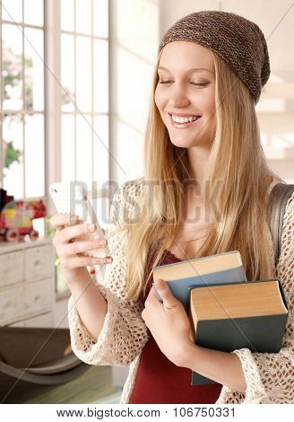 Happy blonde college student holding books, using mobilephone, smiling.