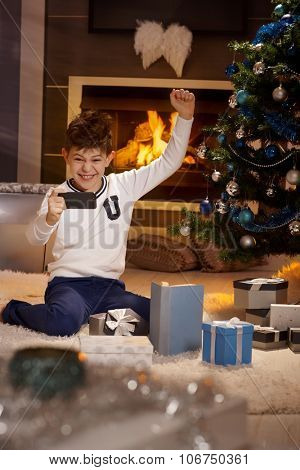 Cute schoolboy playing happy with mobilephone at christmas time.
