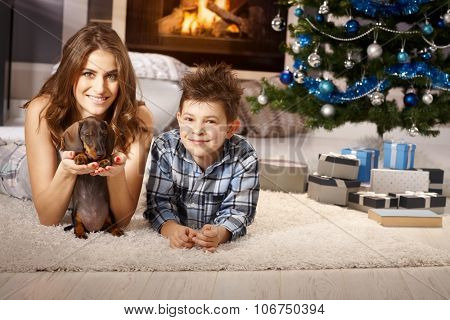 Happy smiling mother and son playing with dachshund puppy at christmas time.