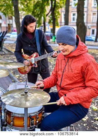 Music street male performers playing percussions on autumn outdoor.