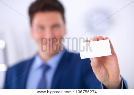 Portrait of young man holding blank white card