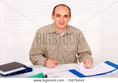Mature man writing and smiling
