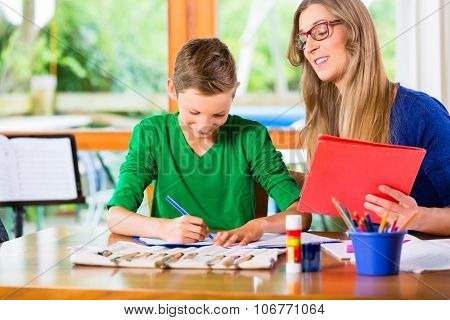 Mother helping son with homework assignment, painting a picture