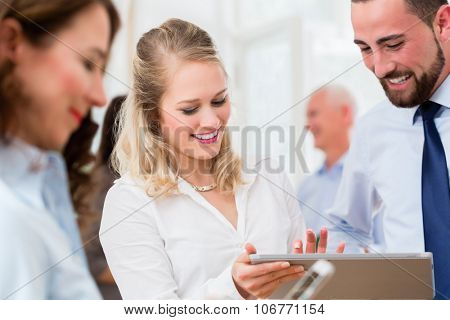 Business people in office having informal meeting and short presentation