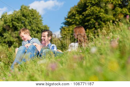 Family cuddling sitting on meadow in summer