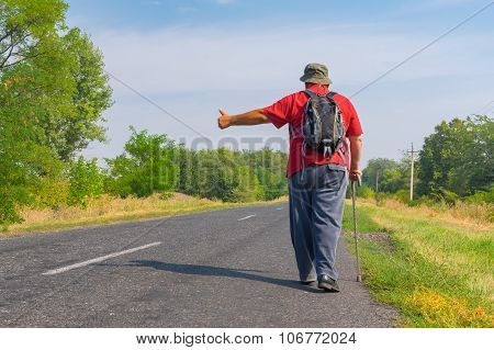 Senior hitchhiker walking on a roadside
