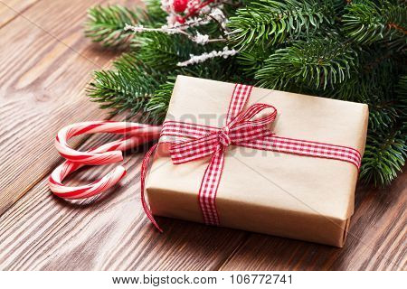 Christmas gift box, candy cane and fir tree branch on wooden table