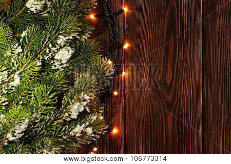 Christmas tree branch and lights on wooden background. View with copy space
