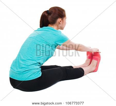 Back view of the girl sitting in front of a warm up exercise.  Rear view people collection.  backside view of person.  Isolated over white background. She clings to his legs stretched before exercise.