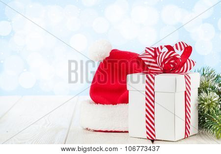 Christmas gift box, santa hat and fir tree branch on wooden table with bokeh background for copy space