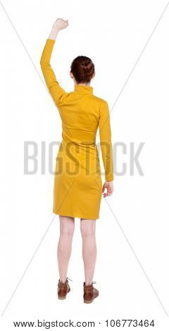 Back view of  woman.  Raised his fist up in victory sign.  Rear view people collection.  backside view of person.  Isolated over white background. Girl in mustard strict dress showing gesture of joy.