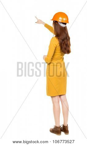 Back view of  pointing young women in helmet. Young girl gesture. Rear view people collection.  backside view of person.  Isolated over white background.