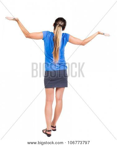 Back view of Beautiful woman in dress looking at wall and Holds  hand up. young blonde girl standing. Rear view people. Isolated over white background.