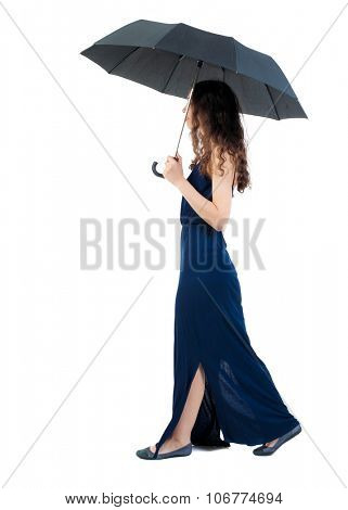 young woman in dress walking under an umbrella. Rear view people collection.  backside view of person.  Isolated over white background.Girl in a blue evening dress comes under the umbrella left.