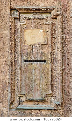 Vintage mail slot in a wooden door