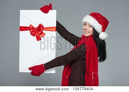 Woman in Santa hat holding white banner