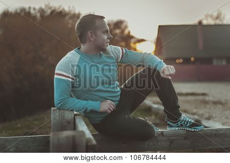 Attractive Man Sitting On Beach In The Evening  After Sport.