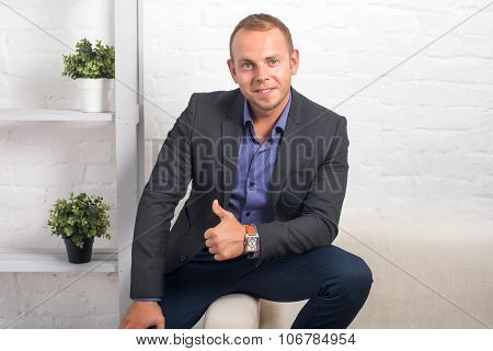 Handsome Businessman Sitting On Couch At Home In The Living Room, Looking Camera