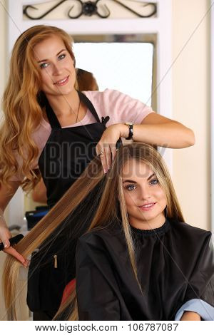 Beautiful Blonde Female Hairdresser Holding Comb And Hair Lock