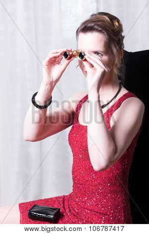 Attractive Woman In Red Dress Looking Trough Magnifying Glass