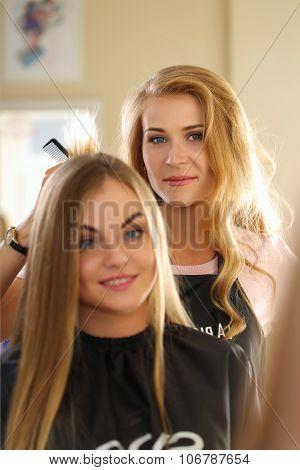 Reflection Of Beautiful Blonde Female Hairdresser Holding Hair Lock