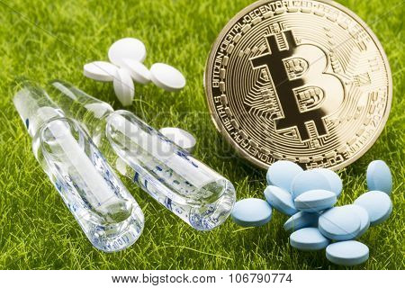 Different pills and ampules with bitcoin coin on the grass background - healthcare cost concept