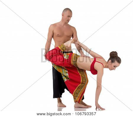 Yoga instructor helps girl to perform asana