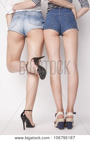 legs of young women, pair  butts in jeans shorts