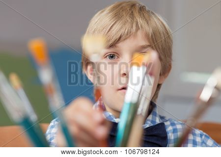 Little Artist Hiding Behind Paintbrushes