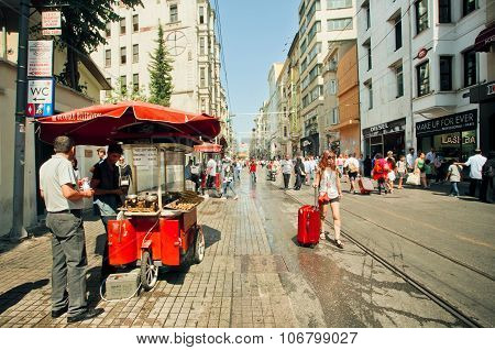 Famous Istiklal Street With Tourists And Traditional Sellers Of Hot Chestnuts