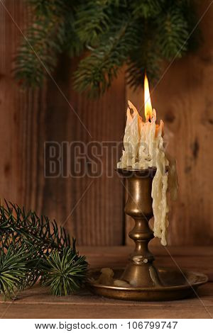 Burning old Candle Vintage Bronze candlestick on wooden background. Spruce branches. Christmas .