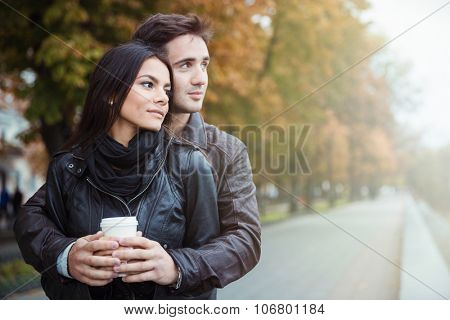 Portrait of a beautiful couple with coffee looking away outdoors