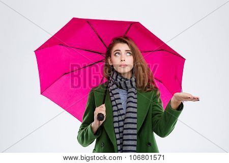 Portrait of a young woman in coat and scarf holding umbrella isolated on a white background
