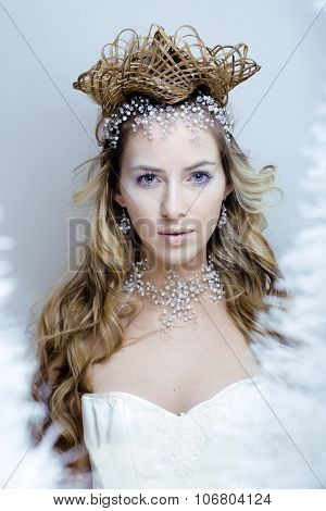 beauty young snow queen in fairy flashes with hair crown on her head close up frozen lashes