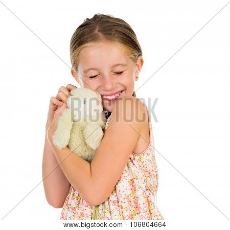 little girl holding toy bunny with her eyes squinted isolated on white background
